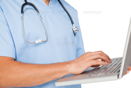 Close-up mid section of a male surgeon using laptopの写真素材 [FYI00001661]