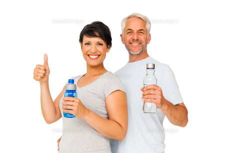Fit couple with water bottles gesturing thumbs upの素材 [FYI00001664]