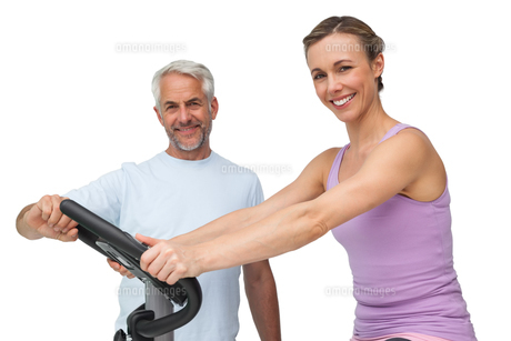 Portrait of a happy woman on stationary bike with trainerの写真素材 [FYI00001670]