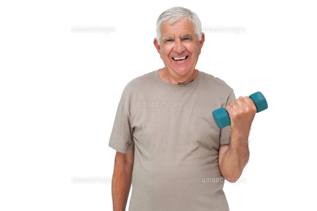 Portrait of a happy senior man exercising with dumbbellの写真素材 [FYI00001672]