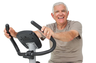 Portrait of a happy senior man on stationary bikeの写真素材 [FYI00001680]