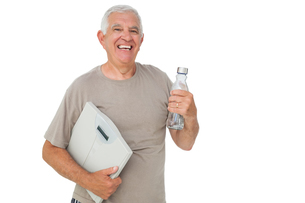 Cheerful senior man with water bottle and scalesの写真素材 [FYI00001681]
