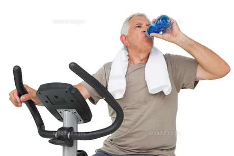 Senior man drinking water on stationary bikeの写真素材 [FYI00001682]