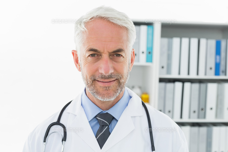 Smiling confident male doctor at medical officeの写真素材 [FYI00001691]