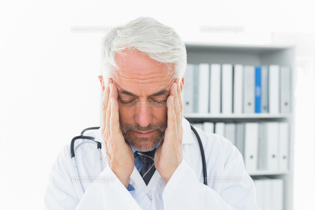 Close-up of a male doctor with severe headacheの写真素材 [FYI00001692]