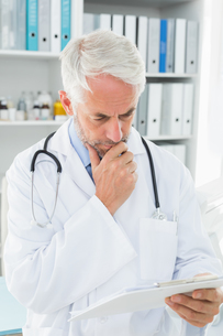 Concentrated male doctor looking at reportsの写真素材 [FYI00001696]