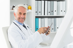Smiling male doctor using digital tablet at medical officeの写真素材 [FYI00001698]