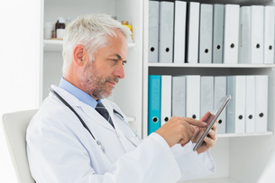 Concentrated doctor using digital tablet at medical officeの写真素材 [FYI00001699]
