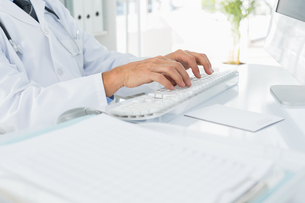 Mid section of doctor using computer keyboard at medical officeの写真素材 [FYI00001701]