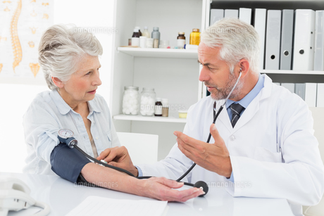 Doctor taking the blood pressure of his retired patientの写真素材 [FYI00001702]