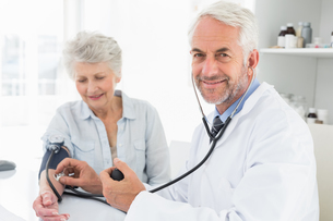 Doctor taking the blood pressure of his retired patientの写真素材 [FYI00001705]