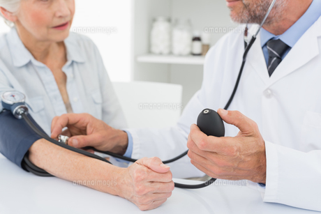 Mid section of doctor taking blood pressure of his patientの写真素材 [FYI00001707]