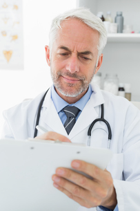 Concentrated male doctor writing reportsの写真素材 [FYI00001714]