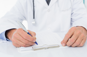 Mid section of a doctor writing on clipboardの写真素材 [FYI00001716]