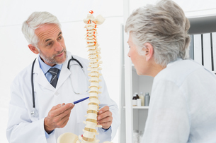 Male doctor explaining the spine to senior patientの写真素材 [FYI00001717]