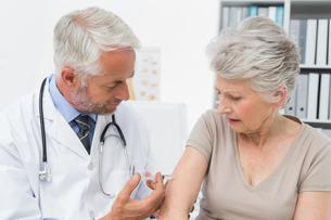 Male doctor injecting senior female patientの写真素材 [FYI00001722]