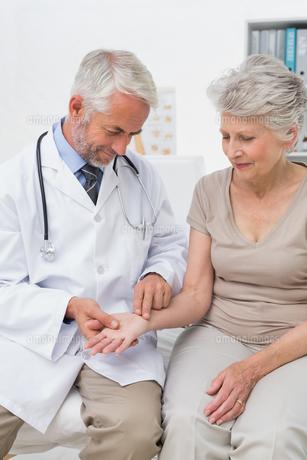 Male doctor taking a senior females pulseの写真素材 [FYI00001723]