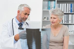 Male doctor explaining x-ray to senior patientの写真素材 [FYI00001724]