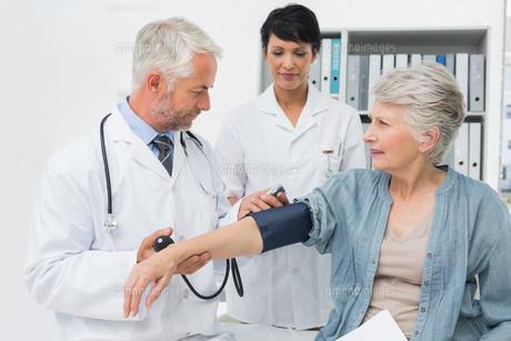 Doctor measuring blood pressure of a senior patientの写真素材 [FYI00001725]