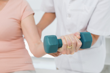Mid section of physiotherapist assisting woman to lift dumbbellの写真素材 [FYI00001726]