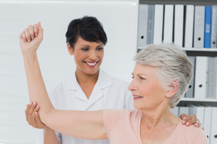 Physiotherapist assisting senior woman to stretch her handの写真素材 [FYI00001727]