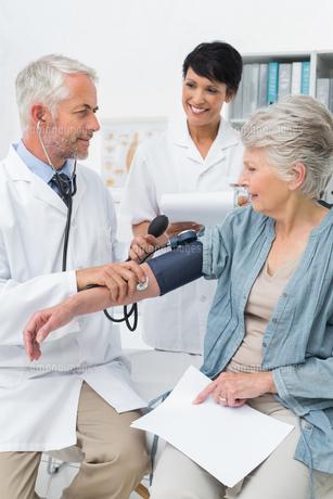 Doctor measuring blood pressure of a senior patientの写真素材 [FYI00001729]