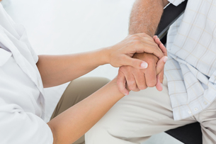 Mid section of a doctor holding patients handの写真素材 [FYI00001730]