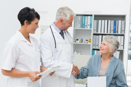 Smiling female patient and doctor shaking handsの写真素材 [FYI00001731]