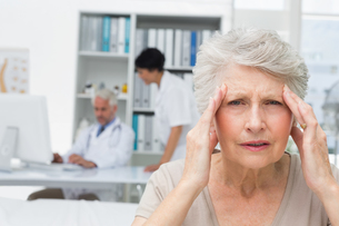 Senior patient suffering from headache with doctors at medical officeの写真素材 [FYI00001732]