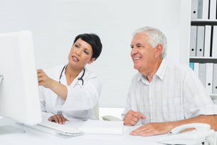 Doctor with male patient reading reports on computerの写真素材 [FYI00001742]