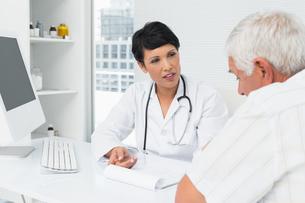 Female doctor explaining reports to senior patientの写真素材 [FYI00001745]