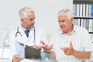 Male doctor explaining x-ray report to senior patientの写真素材 [FYI00001746]