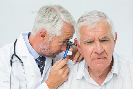 Male doctor examining senior patient's earの写真素材 [FYI00001747]