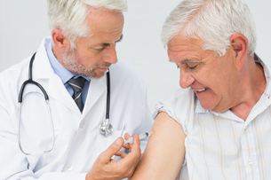 Doctor injecting senior male patientの写真素材 [FYI00001748]