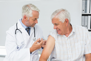 Doctor injecting senior male patientの写真素材 [FYI00001750]
