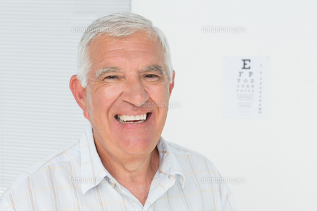 Smiling senior man with eye chart in the backgroundの写真素材 [FYI00001761]
