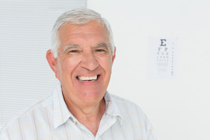 Smiling senior man with eye chart in the backgroundの素材 [FYI00001761]