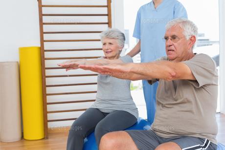 Therapist assisting senior couple with exercisesの写真素材 [FYI00001762]