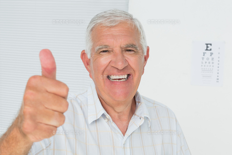Smiling senior man gesturing thumbs up with eye chart in backgroundの素材 [FYI00001763]