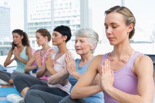 Class sitting with joined hands in a row at yoga classの写真素材 [FYI00001764]
