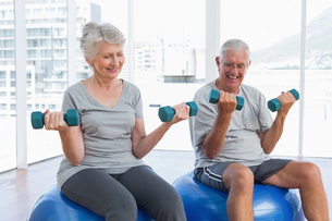 Happy senior couple sitting on fitness balls with dumbbellsの写真素材 [FYI00001766]