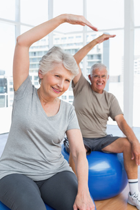 Senior couple doing stretching exercises on fitness ballsの写真素材 [FYI00001767]
