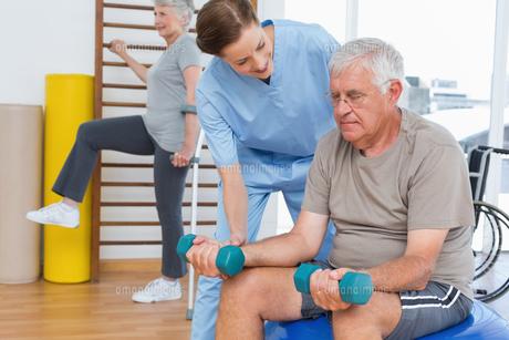 Female therapist assisting senior man with dumbbellsの写真素材 [FYI00001768]