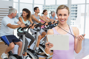Female trainer with people working out at spinning classの写真素材 [FYI00001770]