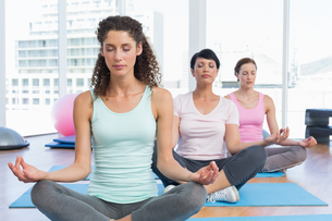 Women in lotus pose with eyes closed at fitness studioの写真素材 [FYI00001771]