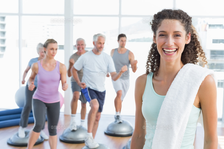 Cheerful woman with people exercising at fitness studioの写真素材 [FYI00001773]