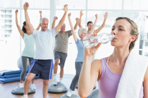 Woman drinking water with people stretching hands at fitness studioの素材 [FYI00001776]