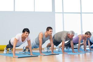 Group doing push ups in row at yoga classの写真素材 [FYI00001781]