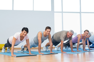 Group doing push ups in row at yoga classの写真素材 [FYI00001784]