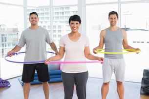 Fitness class holding hula hoops around waist in gymの写真素材 [FYI00001785]